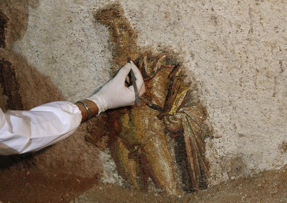 "A worker cleans a mosaic mural depicting Apollo and the Muses found in an archaeological site under the ""Terme di Traiano"" in downtown Rome July 29, 2011. The mosaic was unveiled by the Department of Cultural Affairs on Friday after it was discovered as restoration works are undertaken at Domus Aurea, a large landscaped villa built in ancient Rome. REUTERS/Tony Gentile (ITALY - Tags: SOCIETY)"