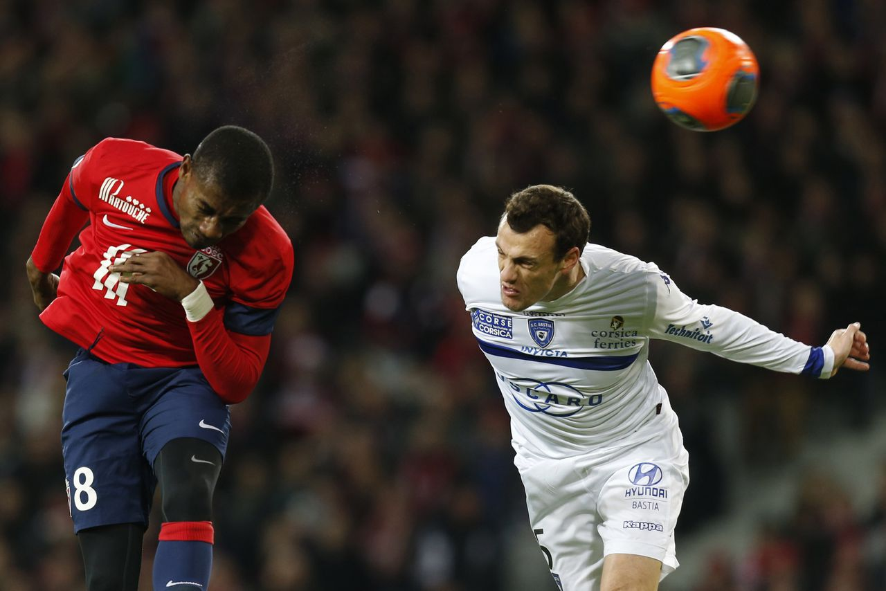 Lille's Salomon Kalou (L) fights for the ball with Bastia' s Sebastien Squillaci during their French Ligue 1 soccer match at Pierre Mauroy Stadium in Villeneuve d'Ascq December 15, 2013. REUTERS/Pascal Rossignol (FRANCE - Tags: SPORT SOCCER)