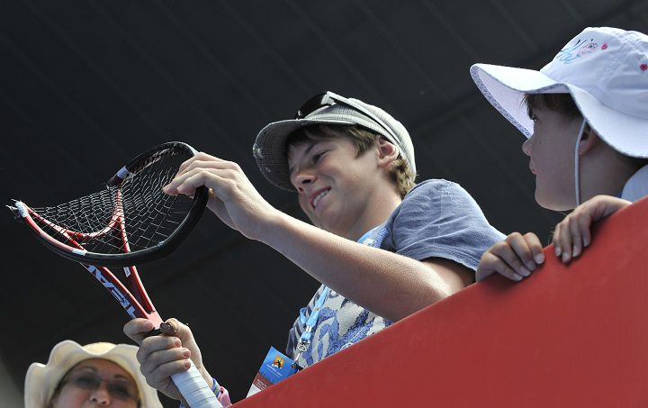 A boy in the crowd holds Stanislas Wawrinka of Switzerland's crushed racquet after Wawrinka smashed it on the ground in reaction to losing a point against Roger Federer of Switzerland during his quarter-final men's singles match on the ninth day of the Australian Open tennis tournament in Melbourne on January 25, 2011. Federer won 6-1, 6-3, 6-3. IMAGE STRICTLY RESTRICTED TO EDITORIAL USE ? STRICTLY NO COMMERCIAL USE AFP PHOTO / PAUL CROCK