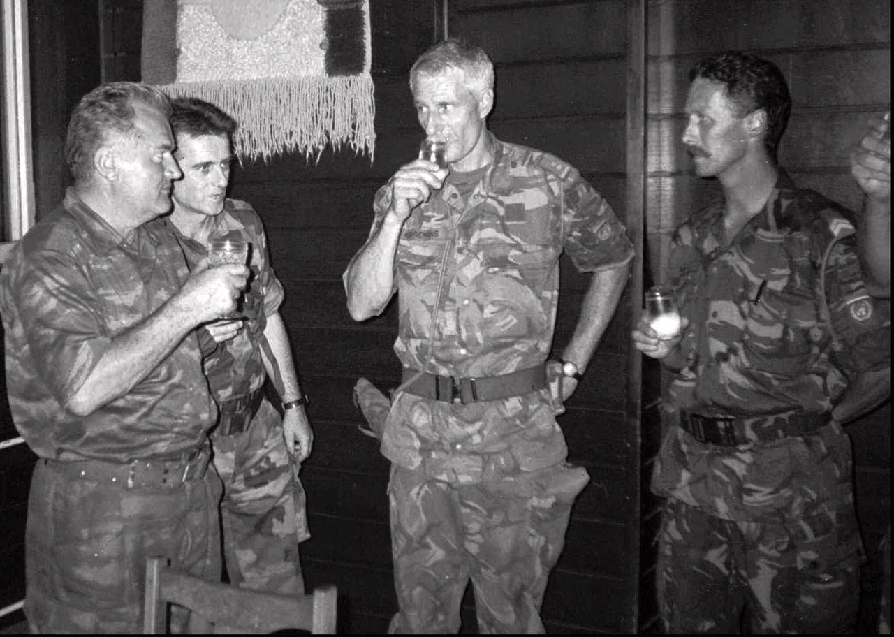 "Bosnian Serb army General Ratko Mladic, left, drinks with Dutch military Col. Ton Karremans, second right, in the Bosnian village of Potocari, in this July 12, 1995 photo. Four years after Serb troops hauled away hundreds of Muslims to their deaths while Dutch peacekeepers looked on, a series of gritty new films about the Bosnian slaughter has rekindled a sense of national rage and shame in the Netherlands. Using an impressive collection of archive footage, Leslie Woodhead recounts the events at Srebrenica in the film ""A Cry From the Grave"" at the annual International Documentary Film Festival in Amsterdam. Among some of the most interesting footage is a Serb military recording where a frightened and timid Karreman is seen virtually pleading for the life of his troops during negotiations with Gen. Mladic. (AP Photo)"
