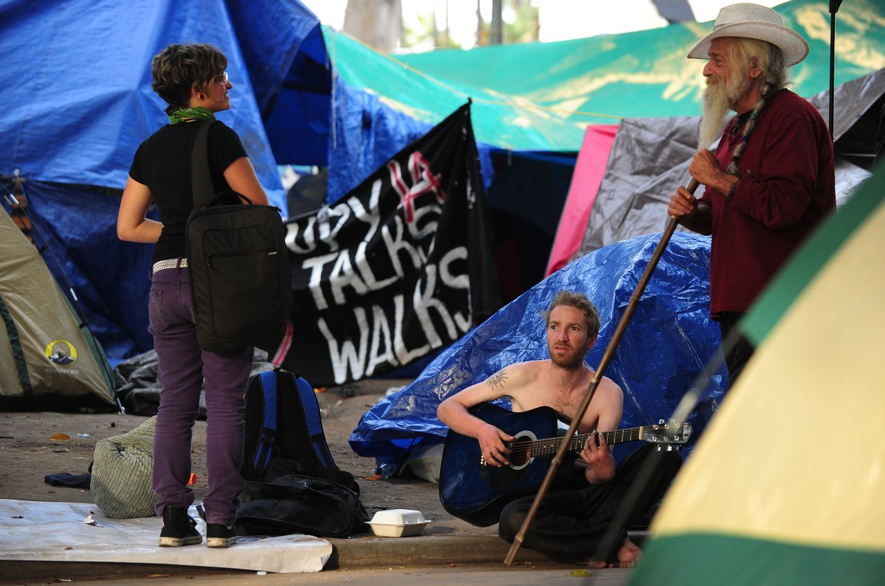 "An anti-Wall Street demonstrator plays his guitar among remianing tents in front of City Hall in downtown Los Angeles on November 28, 2011 where many have been camped out since early October. Hundreds of anti-Wall Street protesters in Los Angeles have vowed to stay put at their downtown camp after defying a deadline to leave, as police mulled how to evict them ""as gently as possible."" A small group of protesters also announced legal action aimed at preventing police from breaking up their encampment in a park surrounding City Hall, which remained in place despite a midnight deadline. AFP PHOTO / Frederic J. BROWN"