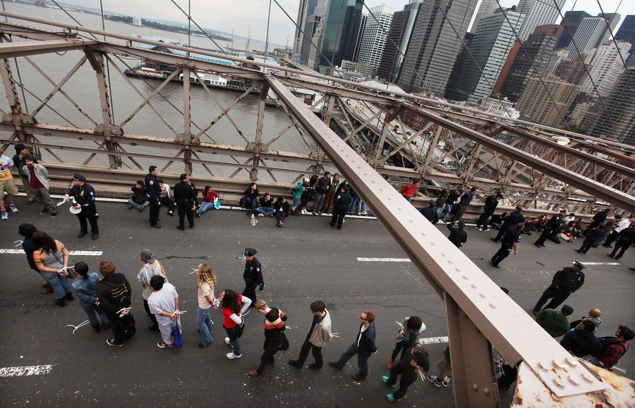 NEW YORK, NY - OCTOBER 01: Demonstrators affiliated with the Occupy Wall Street movement are led away after being arrested when they attempted to cross the Brooklyn Bridge on the motorway on October 1, 2011 New York City. This portion of the bridge is not intended for pedestrians and as the marchers attempted to cross, they were stopped midway by police. Mario Tama/Getty Images/AFP == FOR NEWSPAPERS, INTERNET, TELCOS & TELEVISION USE ONLY ==