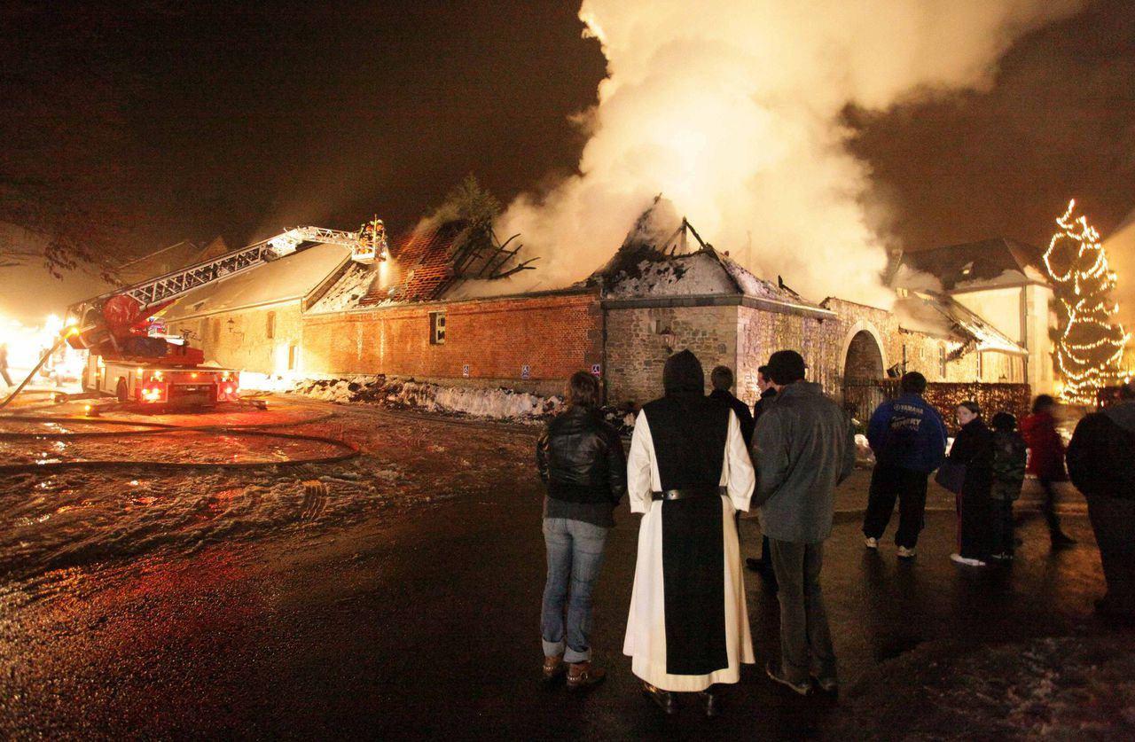 Onlookers watch as firefighters extinguish a fire on the roof of the Abbey Saint Remy in Rochefort December 29, 2010. REUTERS/Thierry Dricot (BELGIUM - Tags: RELIGION DISASTER IMAGES OF THE DAY)