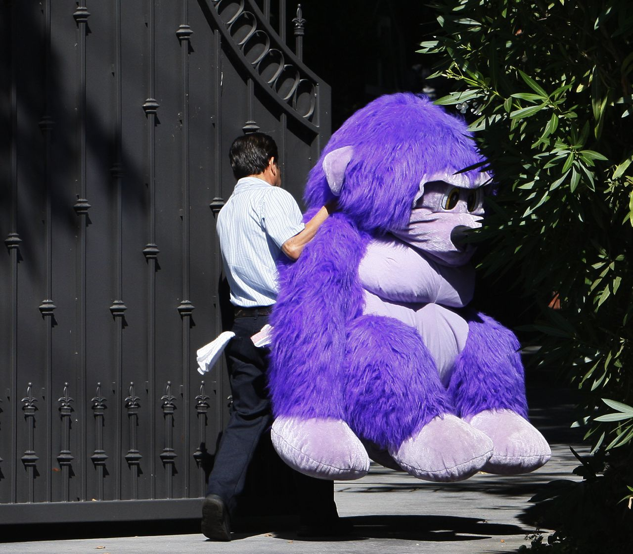 (AP/ Charles Dharapak) A maintenance worker carries a large stuffed purple monkey left for pop star Michael Jackson at the makeshift memorial into the Jackson family residence in Encino, Calif., Tuesday, June 30, 2009. (AP Photo/Charles Dharapak)