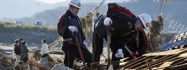 Rescue workers look for missing people in houses destroyed by a tsunami in Yamamoto, Miyagi Prefecture in northeastern Japan March 12, 2011. Japan confronted devastation along its northeastern coast on Saturday, with fires raging and parts of some cities under water after a massive earthquake and tsunami that likely killed at least 1,000 people. REUTERS/Kyodo
