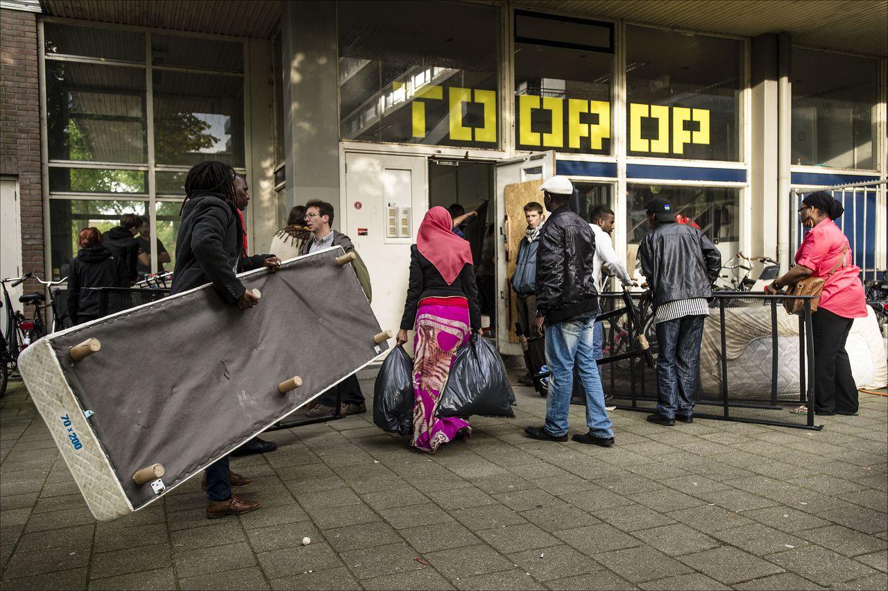 Asielzoekers sjouwen hun spullen naar binnen in het Toorop gebouw in Amsterdam.