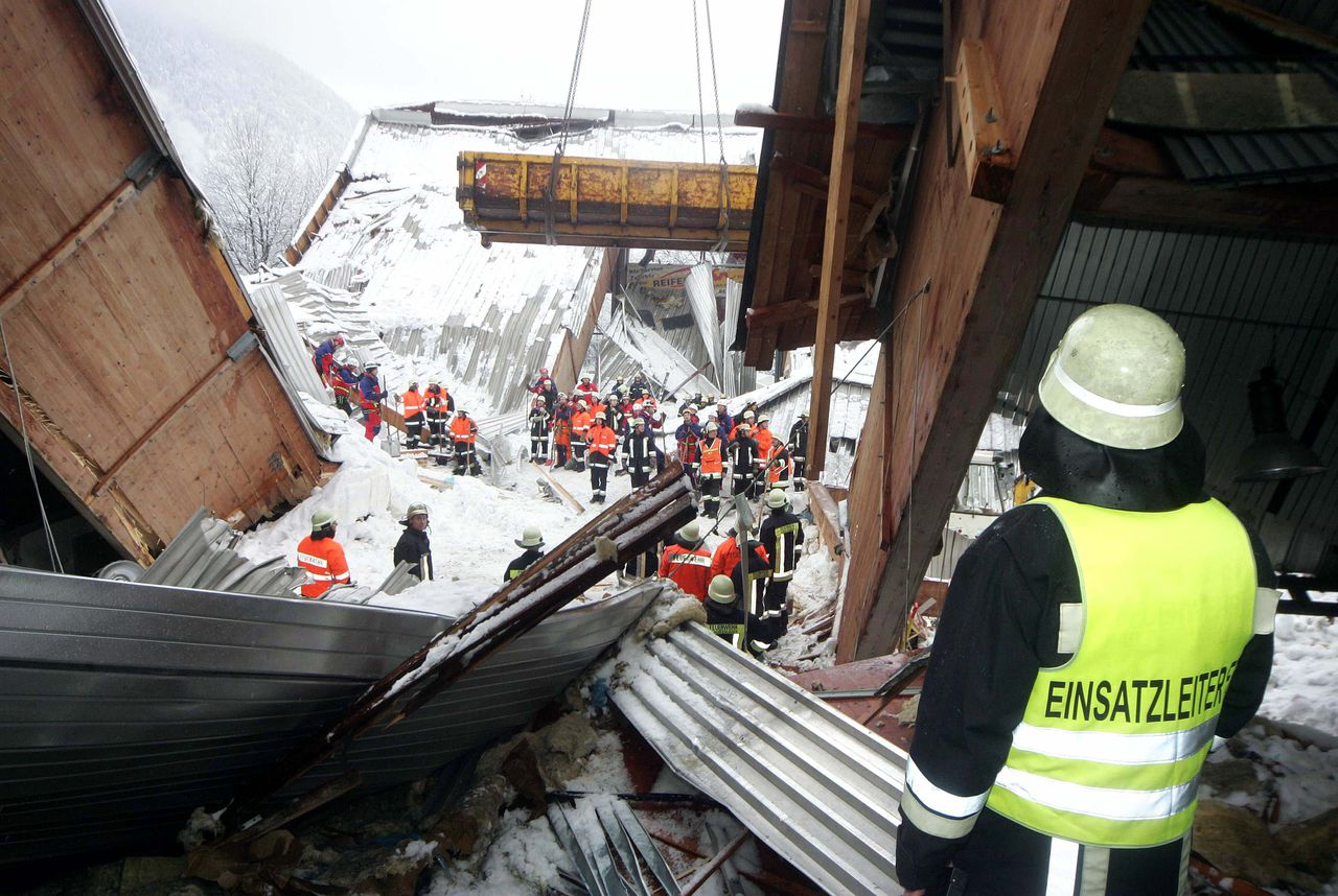 Emergency workers attempt to clear snow and wreckage from the collapsed ice skating rink at Bad Reichenhall January 3, 2006. Up to 15 people, including children, were killed or feared dead after the roof of a skating rink in southern Germany collapsed in heavy snow, police and officials said on Tuesday. Schools in the region were on holiday and many children and their parents were inside the building in the Bavarian town of Bad Reichenhall, by the Austrian border, when the roof, weighed down by masses of snow, fell in on Monday. REUTERS/Johannes Simon/Pool