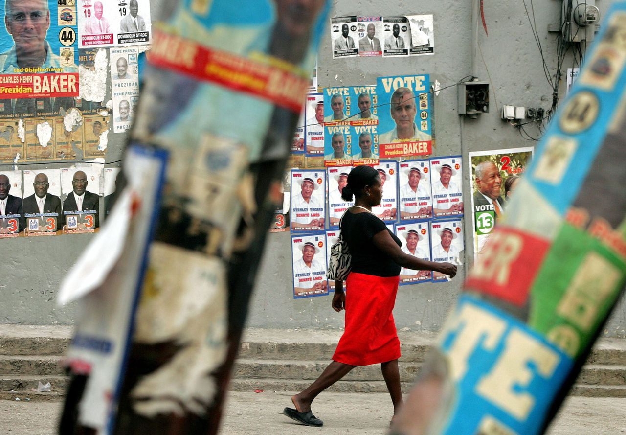 Een vrouw loopt in de Haïtiaanse hoofdstad Port-au-Prince langs een muur met verkiezingsposters. Morgen gaat de bevolking van het straatarme land naar de stembus. Foto Reuters A Haitian woman walks past posters of presidential candidates in Port-au-Prince, Haiti February 5, 2006. Rife with fear of an explosion of violence, Haiti will vote on a new president on Tuesday to replace its last elected leader, Jean-Bertrand Aristide, ousted two years ago in a bloody rebellion. REUTERS/Shannon Stapleton