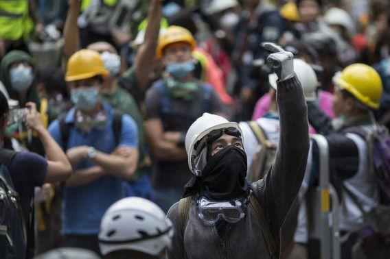 Een demonstrant in Hongkong steekt een middelvinger op naar de politie, december 2014.