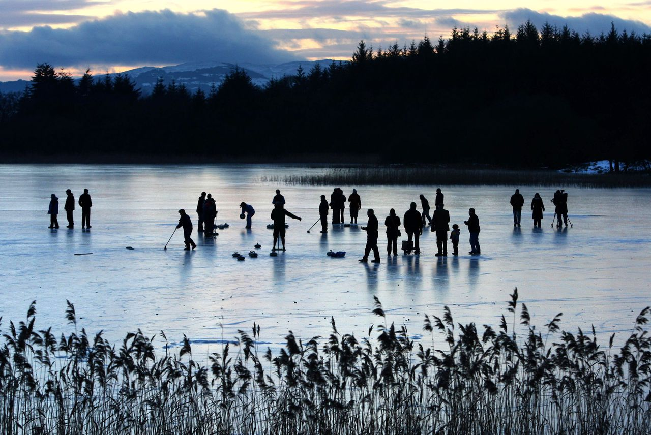 Port of Menteith Curling Club members are silhouetted during a curling match on the Lake of Menteith, in Port of Menteith, Scotland, Monday, Jan. 4, 2010. (AP Photo/PA, Andrew Milligan) ** UNITED KINGDOM OUT, NO SALES, NO ARCHIVE **