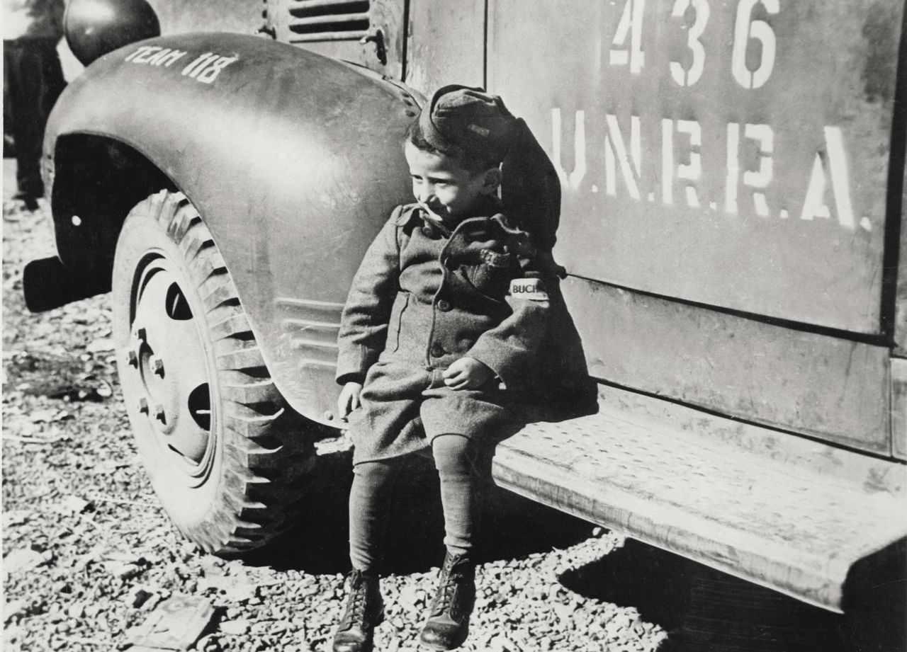 Close up of a child boy who survived the concentration camp in Buchenwald. He wears a small uniform and is sat down on the foot-board of a lorry of UNRRA (United Nations Relief and Rehabilitation Administration). Germany, 1945. (Photo by Mondadori Portfolio via Getty Images)