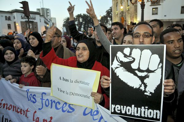 Moroccan people gather to show their solidarity with the Egyptian protesters, following the resignation of President Hosni Mubarak, during a protest in Rabat, Morocco, on Friday, Feb. 11, 2011. At centre women hold banner which reads ''Knock down dictator, hurray democracy''. (AP Photo/STR)