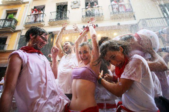 """Revellers are showered with water during the start of the San Fermin Festival in Pamplona July 6, 2011. The annual festival, best known for its daily running of the bulls, kicked off on Wednesday with the traditional """"Chupinazo"""" rocket launch and will run until July 14. REUTERS/Joseba Etxaburu (SPAIN - Tags: SOCIETY)"""