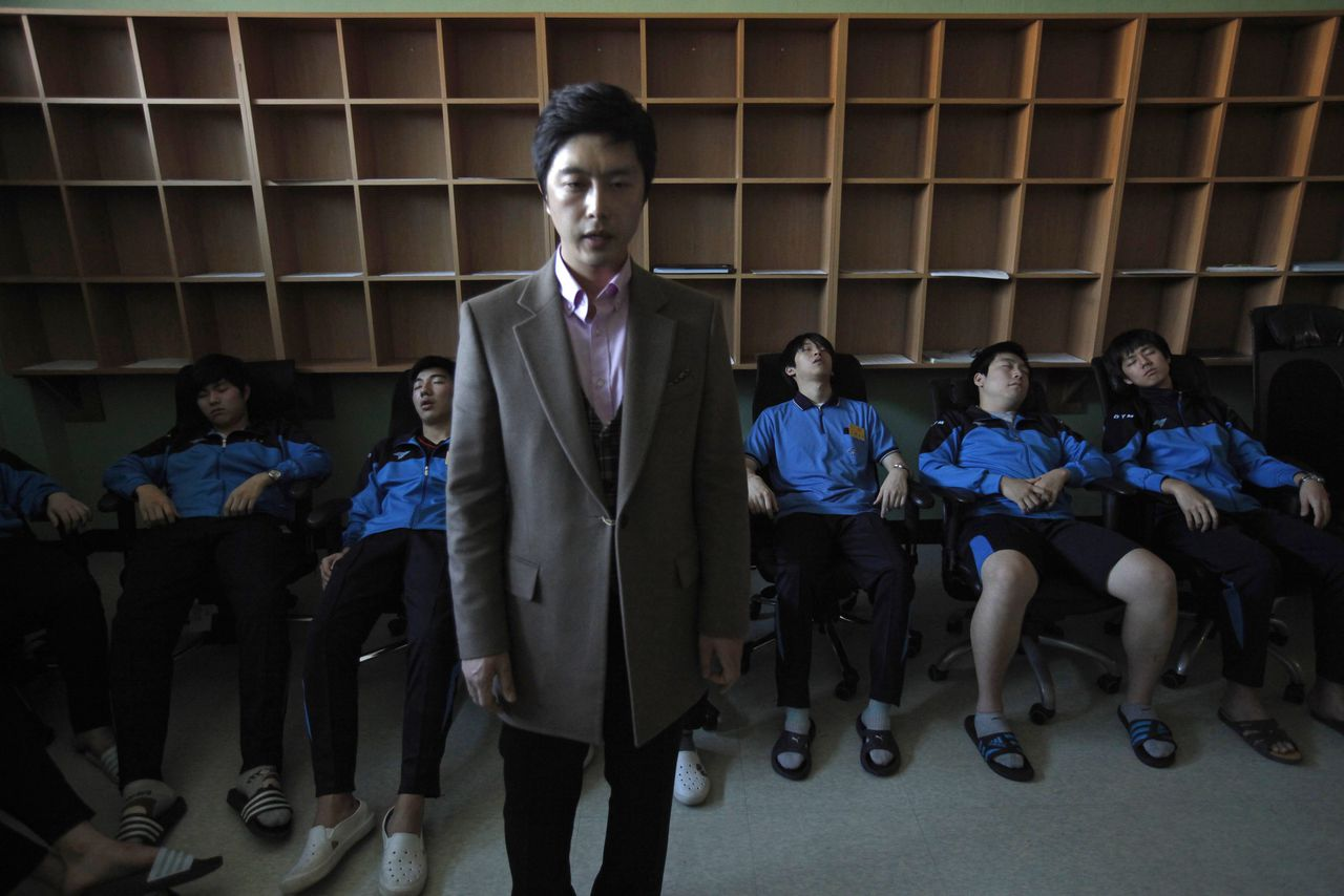 """A therapist hypnotizes students retaking the college entrance exams, during a meditation session at Deung Yong Moon Boarding School in Kwangju, some 40 km (25 miles) southeast of Seoul October 30, 2012. South Korea's exam hell is an annual event so full of pressure that many students are driven to despair, with some even taking their own lives. Some 140,000 of the test takers signed up for this year's entrance exam on November 8, 21 percent of the total, are high school graduates, according to government data. The really determined, or desperate, may decide to spend nine months at one of 40 private boarding schools like Deung Yong Moon (""""Gateway to Success"""") to dedicate their waking hours for the test. Picture taken October 30, 2012. REUTERS/Kim Hong-Ji (SOUTH KOREA - Tags: EDUCATION SOCIETY)"""