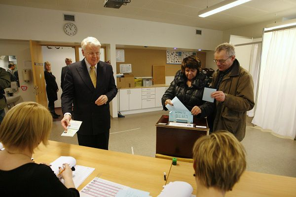Iceland's President Olafur Ragnar Grimsson (L) shows his identification papers before voting in the Icesave referendum in Reykjavik April 9, 2011. Icelanders began voting on Saturday whether to approve a plan to repay debts to Britain and the Netherlands with opinion polls suggesting another rejection, dampening hopes for progress in the island's economic recovery. REUTERS/Ingolfur Juliusson (ICELAND - Tags: POLITICS ELECTIONS)