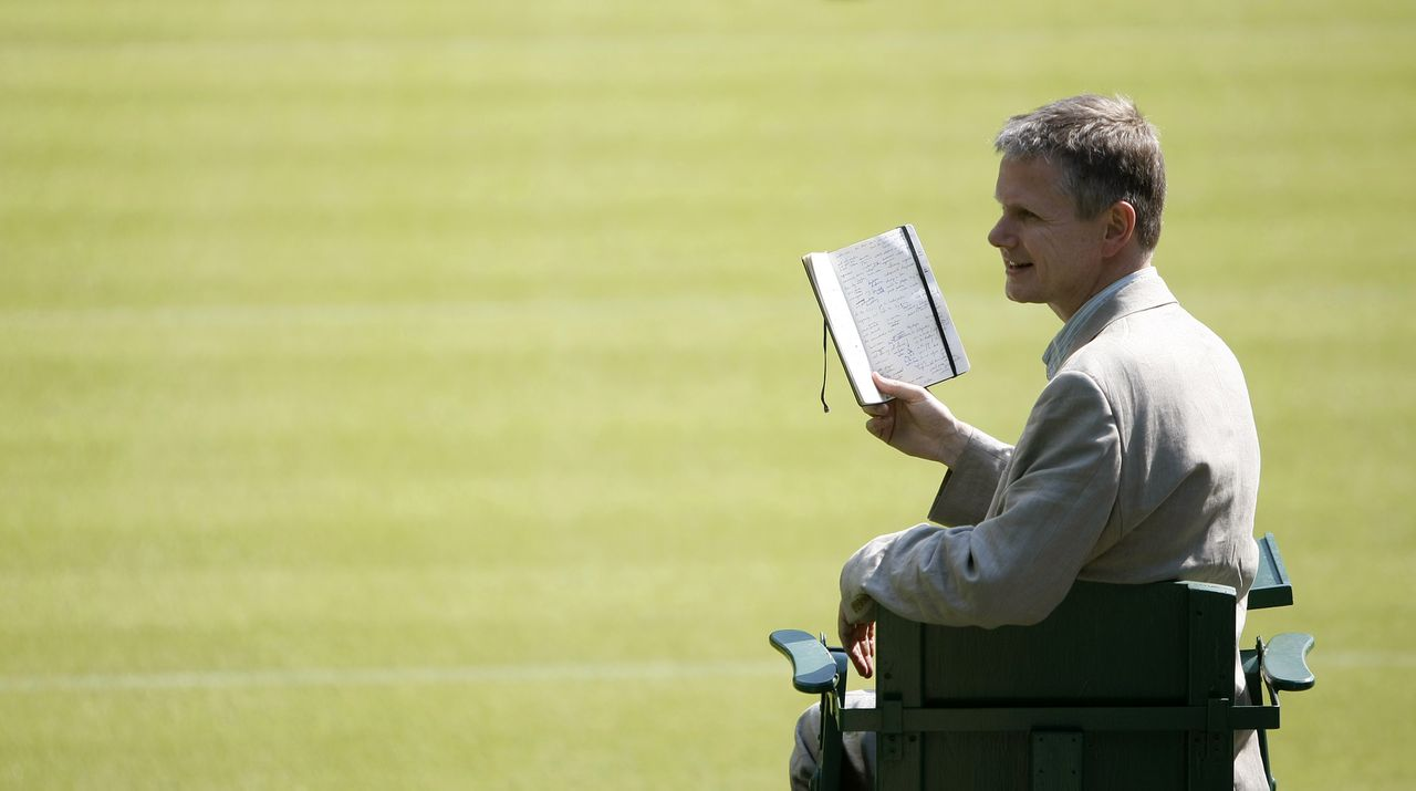 """Matt Harvey, Wimbledons dichter, in de scheidsrechtersstoel met zijn zwarte notitieboekje. Foto AP Matt Harvey, the first Wimbledon tennis """"Championships Poet,"""" sits in the umpire's chair as he poses for the cameras on Centre Court at Wimbledon, England, Tuesday, May 18, 2010. Harvey has been tasked with writing the poems """"on all things Wimbledon,"""" which the All England Club said includes everything """"from umpires and racket stringers to the ball boys and ball girls; from the grass and its bounce to rain and the roof; strawberries and cream and all the unfolding drama of the matches and players."""" (AP Photo/Alastair Grant)"""