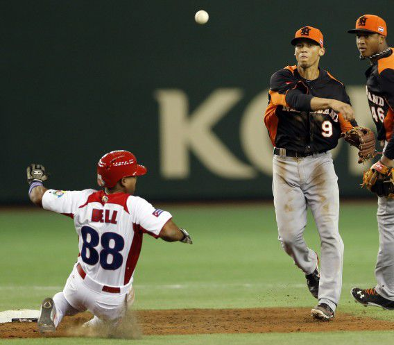Netherlands' shortstop Andrelton Simmons makes completing a double play as Cuba's rightfielder Alexei Bell slide into the second base in the in the third inning of their World Baseball Classic second round game in Tokyo, Japan, Friday, March 8, 2013. (AP Photo/Koji Sasahara)