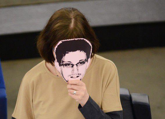 De Duitse Europarlementariër Rebecca Harms houdt een masker voor van Edward Snowden tijdens een zitting over het afluisteren door de NSA van Europese burgers.