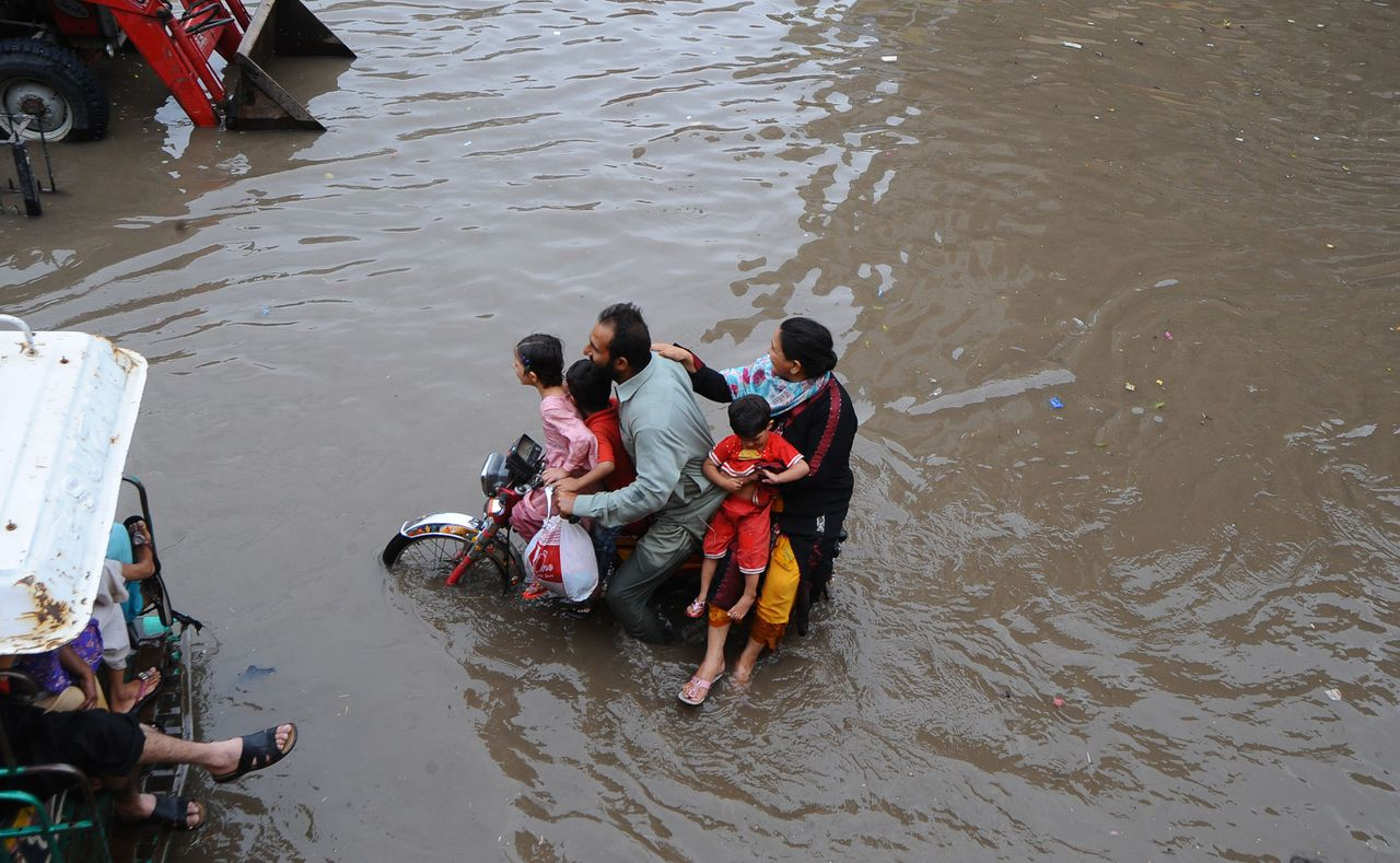 A Pakistani commuter rides on a flooded street after monsoon rain in Lahore on July 3, 2011. Pakistan warned that floods triggered by monsoon rains could affect millions more people this year, but claimed it was better prepared after a massive humanitarian crisis in 2010. Monsoon-triggered floods in 2010 affected up to 21 million people and killed an estimated 1,750 people, causing an estimated 10 billion USD in losses and hammering the already depressed economy. AFP PHOTO/Arif ALI