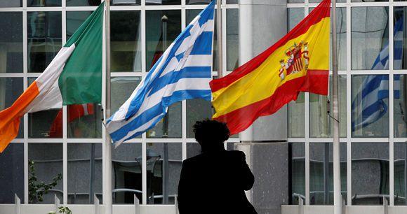 Caption: A pedestrian walks past Irish, Greek and Spanish national flags outside the European Parliament in Brussels August 30, 2011. REUTERS/Francois Lenoir (BELGIUM - Tags: POLITICS)