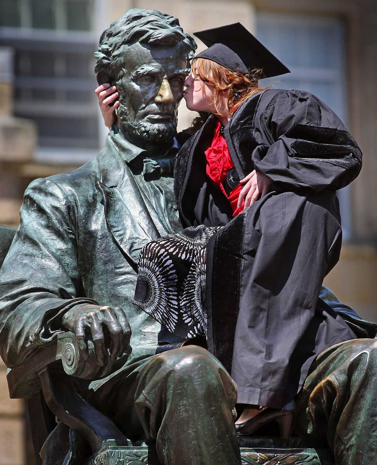 University of Wisconsin-Madison pharmacy school graduate Samantha Miller gives the Abraham Lincoln statue on the UW campus a kiss on Friday, May 18, 2012 in Madison, Wis. With help from family members and friends, students in caps and gowns climbed into the lap of the statue, the top which is more than 13 feet off the ground, to have their pictures taken in a graduation tradition on Bascom Hill, the historic center of campus. (AP Photo/Wisconsin State Journal, Craig Schreiner)