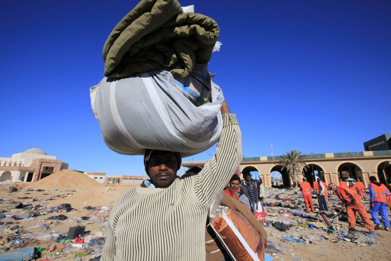 A Bengladeshi migrant worker who fled the unrest in Libya lines up at Libyan side of the Libyan and Tunisian border crossing of Ras Jdir March 2, 2011. REUTERS/Zohra Bensemra (TUNISIA - Tags: POLITICS CIVIL UNREST)
