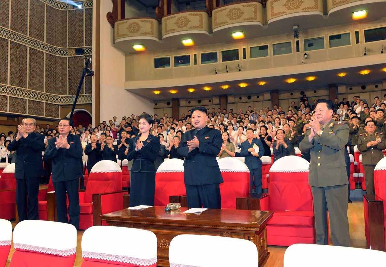 "---EDITORS NOTE--- RESTRICTED TO EDITORIAL USE - MANDATORY CREDIT ""AFP PHOTO / KCNA VIA KNS"" - NO MARKETING NO ADVERTISING CAMPAIGNS - DISTRIBUTED AS A SERVICE TO CLIENTS This picture, taken on July 6, 2012 by North Korean official Korean Central News Agency and released on July 9, shows North Korean leader Kim Jong Un (C), accompanied by a young woman, enjoying a demonstration performance given by the newly organized Moranbong band in Pyongyang. AFP PHOTO / KCNA via KNS"