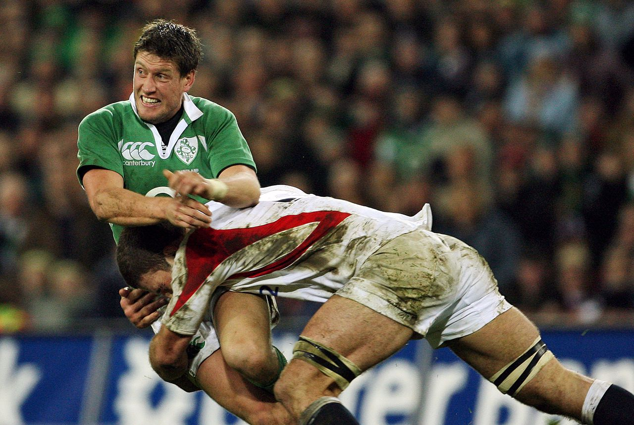 De Ier Ronan O'Gare (links) was tegen Engeland goed voor 21 punten. Mede door zijn inbreng werd de Engelsen een historische nederlaag (43-13) toegebracht. Foto AFP Ireland's Ronan O'Gara (L) is tackled by an unidentified English player during the 6 Nations Rugby union game between Ireland and England at Croke Park stadium, 24 February 2007. Ireland won 43-13. The history of the 82,500-capacity arena that was, until France played the first rugby union international there two weeks earlier, an exclusive citadel for Ireland's traditional sports, is rich in the folklore of hurling and Gaelic football. It is also scarred by the events of November 19, 1920, the day when 14 Irish citizens were shot dead by British soldiers in the stadium in reprisal for the IRA's assassination of British intelligence officers earlier the same day. AFP PHOTO / JOHN D MCHUGH