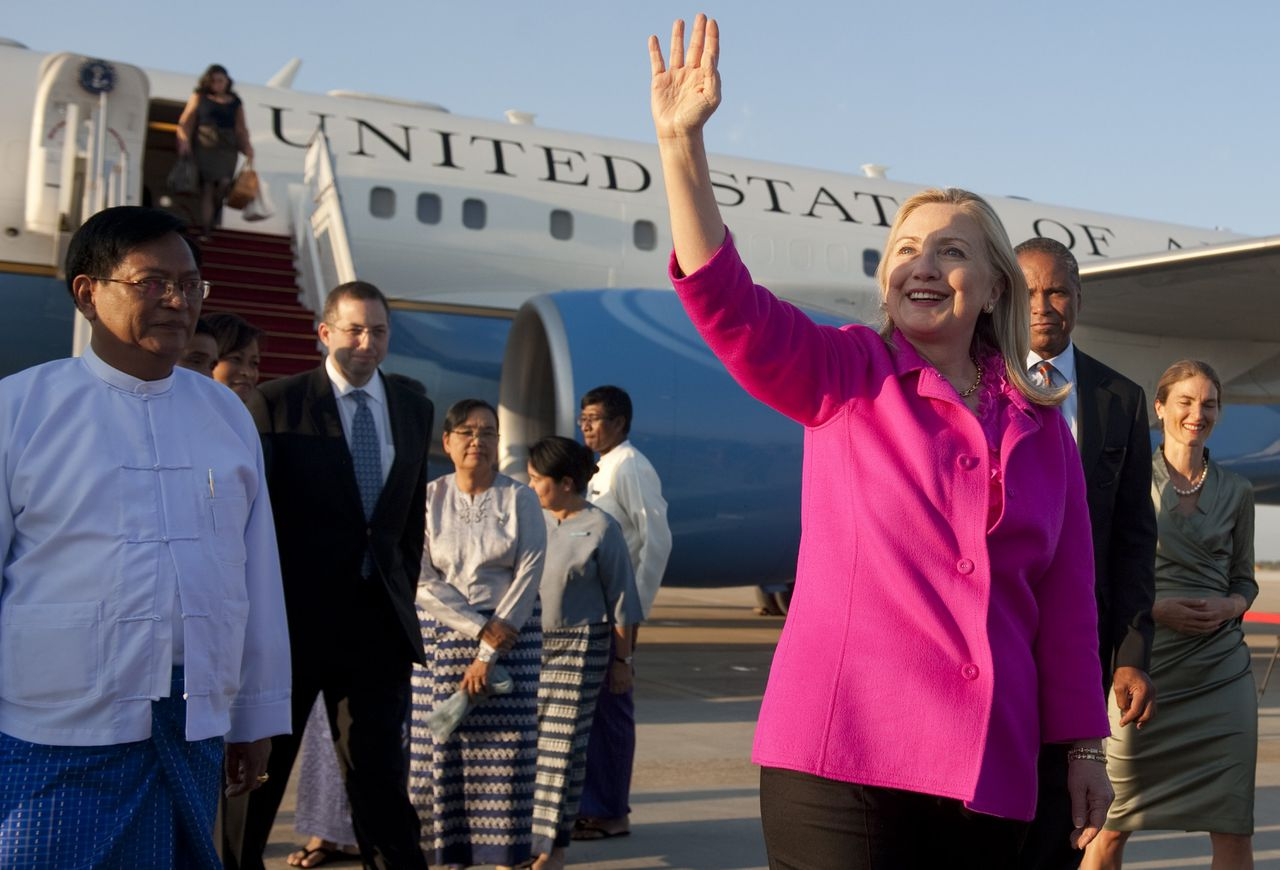 "US Secretary of State Hillary Clinton (R) waves alongside Myanmar Deputy Foreign Minister Myo Myint (L) upon her arrival in Naypyidaw on November 30, 2011. Secretary of State Hillary Clinton arrived in Myanmar November 30 on the first top-level US visit for half a century, seeking to encourage a ""movement for change"" in the military-dominated nation. AFP PHOTO / POOL / Saul LOEB"
