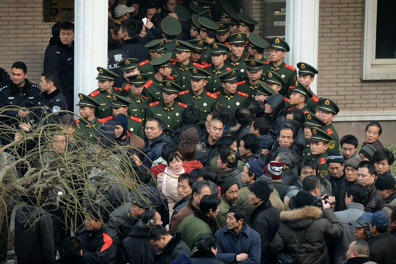 Chinese paramilitary police block access to the residence of a construction firm boss after a group of up to 50 migrant workers stormed past security at the Qijiayuan Diplomatic Compound to protest against what they claim is an unpaid new year bonus, in Beijing on January 14, 2013. Labour unrest and disputes are common before the Chinese New Year when migrant workers are paid for their full years work in a lump sum before heading home to their famillies in outer provinces of the country. TOPSHOTS AFP PHOTO/Mark RALSTON
