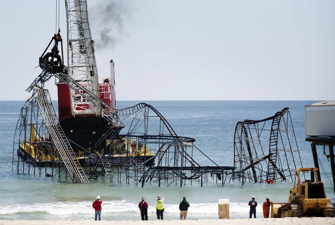 Workers use a crane to remove remnants of the Jet Star roller coaster that have been left in the ocean after Superstorm Sandy hit Seaside Heights last year, in New Jersey, May 14, 2013. Crews on Tuesday began dismantling and removing the Jet Star and other amusement park rides submerged nearby. The cleanup was expected to take about 48 hours, according to Casino Pier, which owns the rides. REUTERS/Lucas Jackson (UNITED STATES - Tags: DISASTER TPX IMAGES OF THE DAY)