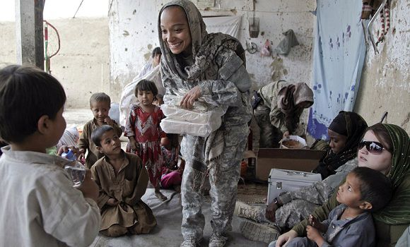 Caption: In this image released by the Defense Department, a team leader for a U.S. Special Operations Cultural Support Team, hands out utensils during a women's shura held at a local compound in the village of Oshay, Uruzgan province, Afghanistan, May 4, 2011. With the support of U.S. special operation forces, the CST and Female Treatment Team are working closely together in order to bring health education to women in the area, as well as give them a voice in the district. (AP Photo/DoD)