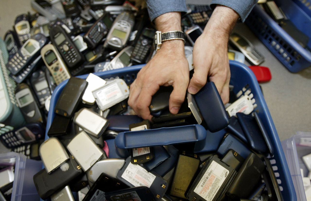 "A worker at CollectiveGood (cq) in Tucker, Ga., sorts through old cell phones and cell phone batteries for recycling Wednesday, April 20, 2005. When Earth Day dawned in 1970, optimistic environmentalists said emerging technologies would help reduce the nation's reliance on coal, oil, insecticides and other toxins. But 35 years later, a big part of the problem appears to be technology itself. Tons of computers, monitors, televisions and other electronic gizmos that contain hazardous chemicals, or ""e-waste,"" may be poisoning people and ground water. Activists say the nation's biggest environmental problem may be the smallest devices, and this week they're launching campaigns to increase awareness about recycling cell phones, music players, handheld gaming consoles and other electronics. (AP Photo/John Bazemore)"