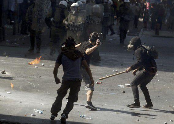 Een demonstrant gooit een steen naar de oproerpolitie op het Syntagmaplein in Athene tijdens de staking uit protest tegen de bezuinigingen van de regering.