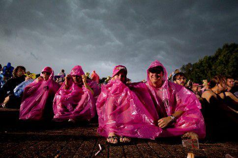 Pinkpopbezoekers zoeken tijdens de editie van 2014 bescherming tegen het noodweer.