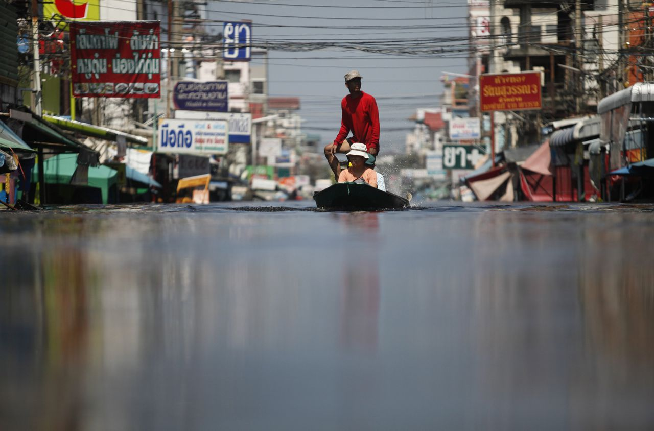 Residents evacuate from their flooded town, north of Bangkok October 25, 2011. Thailand announced a five-day holiday on Tuesday to give people to the chance to escape floods closing in on Bangkok as authorities ordered the immediate evacuation of a housing estate on the outskirts of the city after a protection wall gave way. REUTERS/Bazuki Muhammad (THAILAND - Tags: ENVIRONMENT DISASTER)