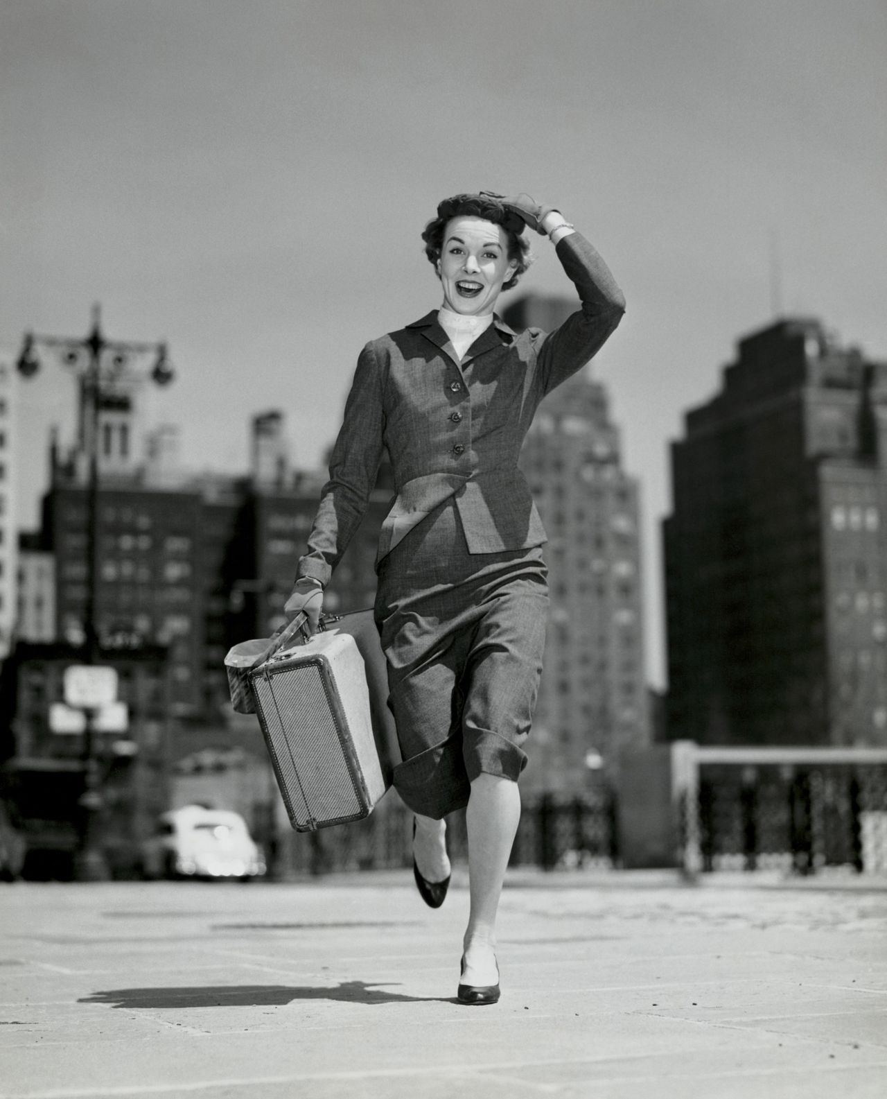 Portrait of young woman carrying suitcase --- Image by © SuperStock/Corbis