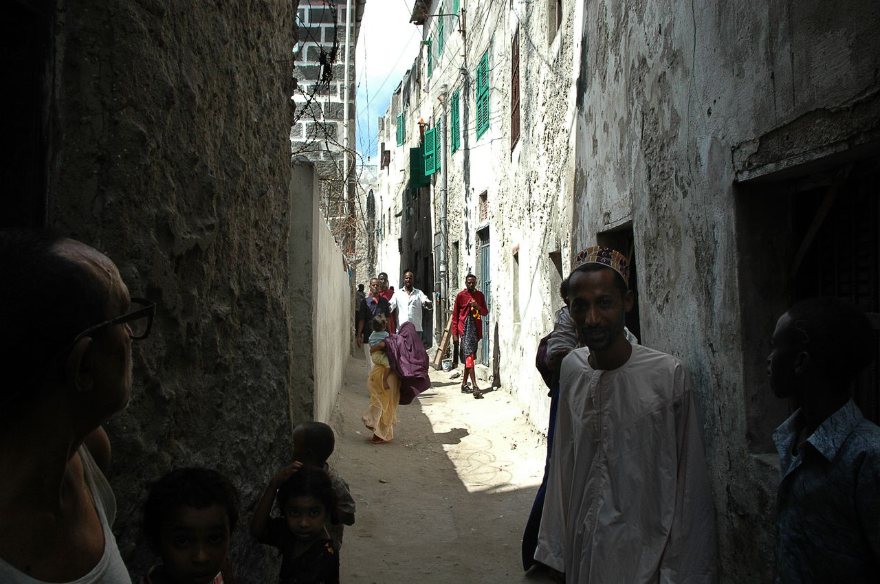 """Steegje in de oude stad van Mogadishu Foto AFP Somalis stroll through the narrow alleys of the old city of Mogadishu 11 January 2007. The United States called 12 January 2007 for an immediate """"inclusive dialogue"""" between all parties in Somalia and the quick deployment of peacekeepers to restore lasting peace in the shattered nation. After weeks of heavy fighting in which a powerful Islamist movement was routed by Ethiopian troops backing the weak Somali government, the US envoy to neighboring Kenya said the steps were the only way to avoid deeper turmoil. AFP PHOTO/STRINGER"""