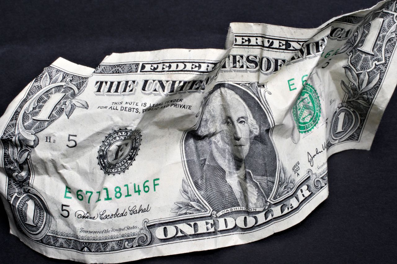 Debat over kredietcrisis A crumpled U.S. one dollar bill is arranged for a photo in New York, U.S., on Monday, Nov. 19, 2007. Crude oil rose above $98 a barrel in New York to a record close after the U.S. dollar declined to a new low against the euro. Photographer: Stephen Hilger/Bloomberg News