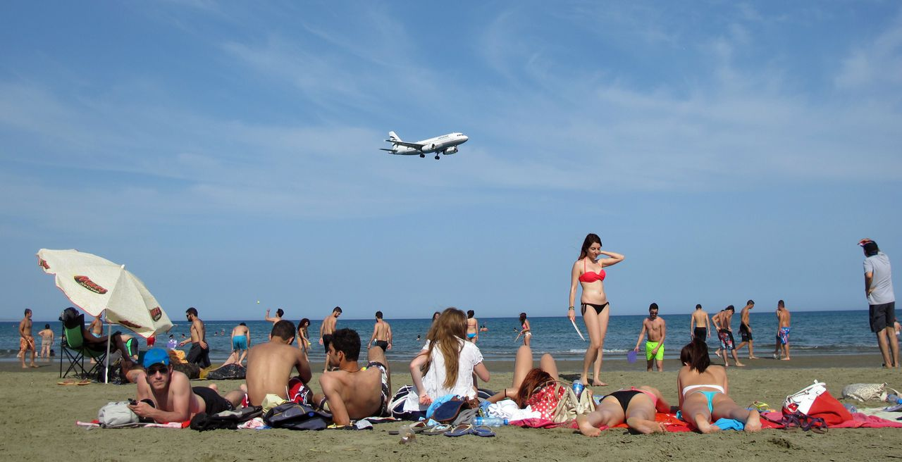 Locals and holiday makers sunbathe at McKenzie beach as a passenger plane approaches Larnaca airport on the southern coast of the east Mediterranean island of Cyprus on June 3, 2012. AFP PHOTO/PATRICK BAZ
