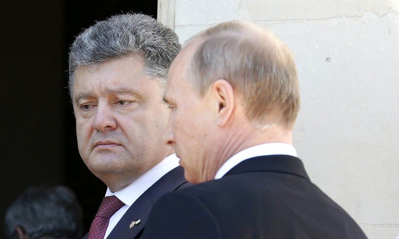 File photo of Ukraine president-elect Petro Poroshenko (C) watching as German Chancellor Angela Merkel (L) talks to Russian President Vladimir Putin during 70th anniversary of the D-Day landings at Benouville Castle, June 6, 2014. After months of ratcheting up pressure on Vladimir Putin, concern is mounting in Berlin and other European capitals that an emboldened Ukraine's military successes in the east are reducing the chances of a face-saving way out of the crisis for the Russian leader. As a result, the focus of German-led diplomatic efforts has shifted, according to senior officials, towards urging restraint from Ukrainian President Petro Poroshenko and averting a humiliating defeat for pro-Russian rebels, a development that Berlin fears could elicit a strong response from Putin. Chancellor Angela Merkel's planned visit to Kiev August 30, 2014, her first since the crisis erupted at the start of the year, is above all a signal of support for Poroshenko, the billionaire confectionary magnate who was elected less than three months ago. REUTERS/Regis Duvignau/Files (FRANCE - Tags: POLITICS)