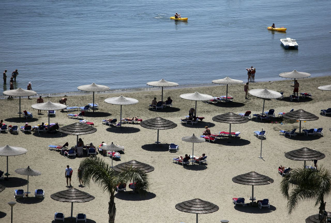 Guests sit under straw parasols as they shelter from the sun while on the private beach of the St. Raphael hotel in Limassol, Cyprus, on Wednesday, April 25, 2012. Cyprus's budget deficit widened to 6.3 percent of gross domestic product last year from 5.3 percent of GDP in 2010, according to an e-mailed statement from the European Union's statistics agency. Photographer: Chris Ratcliffe/Bloomberg