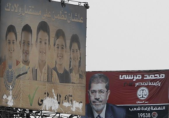 """Name: 2012-05-28T114038Z_01_AMR03_RTRMDNP_3_EGYPT-ELECTION-BROTHERHOOD.JPG Caption: REFILE - ADDING TRANSLATION A campaign election billboard of Mohamed Mursi, the head of the Muslim Brotherhood's political party, is seen in downtown Cairo May 28, 2012. The Brotherhood did what it does better than any other group in Egypt: mobilised a nationwide network to get out the vote, catapulting Mursi into the second round on June 16 and 17 against Ahmed Shafiq, Hosni Mubarak's last prime minister. But the success masks a setback. By its own calculations, the Brotherhood's vote fell by almost half compared to the lower house parliamentary election six months ago. The billboard (L) reads, """"To be relaxed and comfortable for you and your sons, give your vote to NPD"""". To match Feature EGYPT-ELECTION/BROTHERHOOD REUTERS/Amr Abdallah Dalsh (EGYPT - Tags: POLITICS ELECTIONS) IPTC Date: 11:40 28/05/12"""