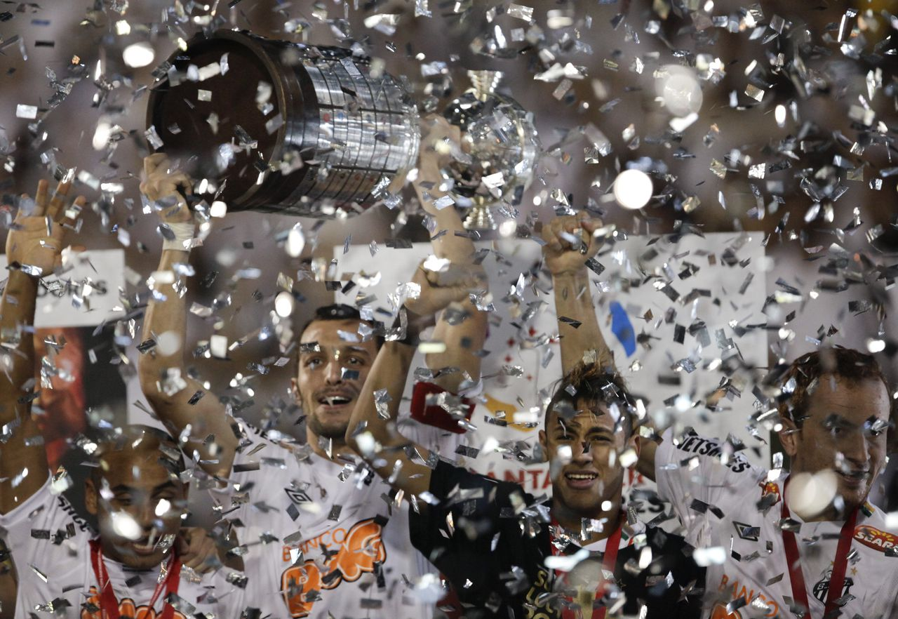 ** CORRECTS FINAL SCORE TO 2-1 ** Brazil's Santos' players celebrate at the end of the Copa Libertadores final soccer match against Uruguay's Penarol in Sao Paulo, Brazil, Wednesday, June 22, 2011. Santos won 2-1. (AP Photo/Victor R. Caivano)