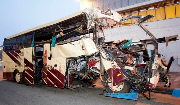 Caption: The wreckage of a tourist bus from Belgium is dragged by a tow truck outside the tunnel of the motorway A9, in Sierre, western Switzerland, early Wednesday, March 14, 2012. 28 people were killed in the bus crash. (AP Photo/Keystone, Laurent Gillieron)