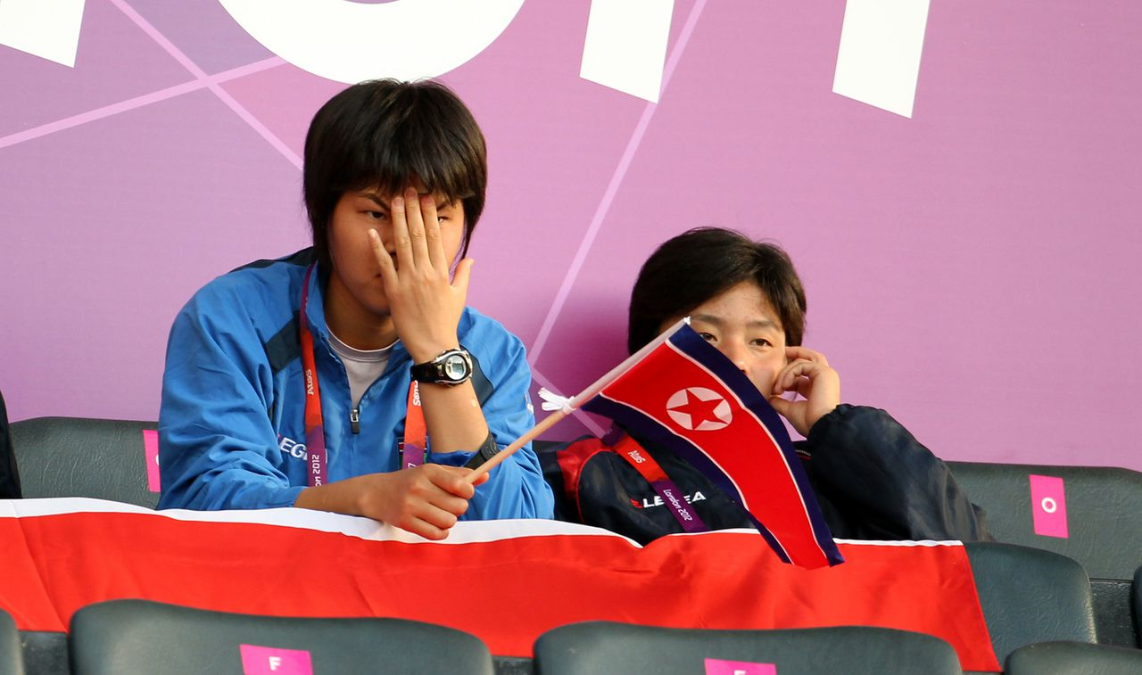 A man waves a North Korean flag in the stands as North Korea's Olympic group G women's soccer match against Colombia is delayed due to an apparent mix up over the nation's flag, at Hampden Park, in Glasgow, on Wednesday July 25, 2012. (AP Photo/Lynne Cameron, PA) UNITED KINGDOM OUT NO SALES NO ARCHIVE