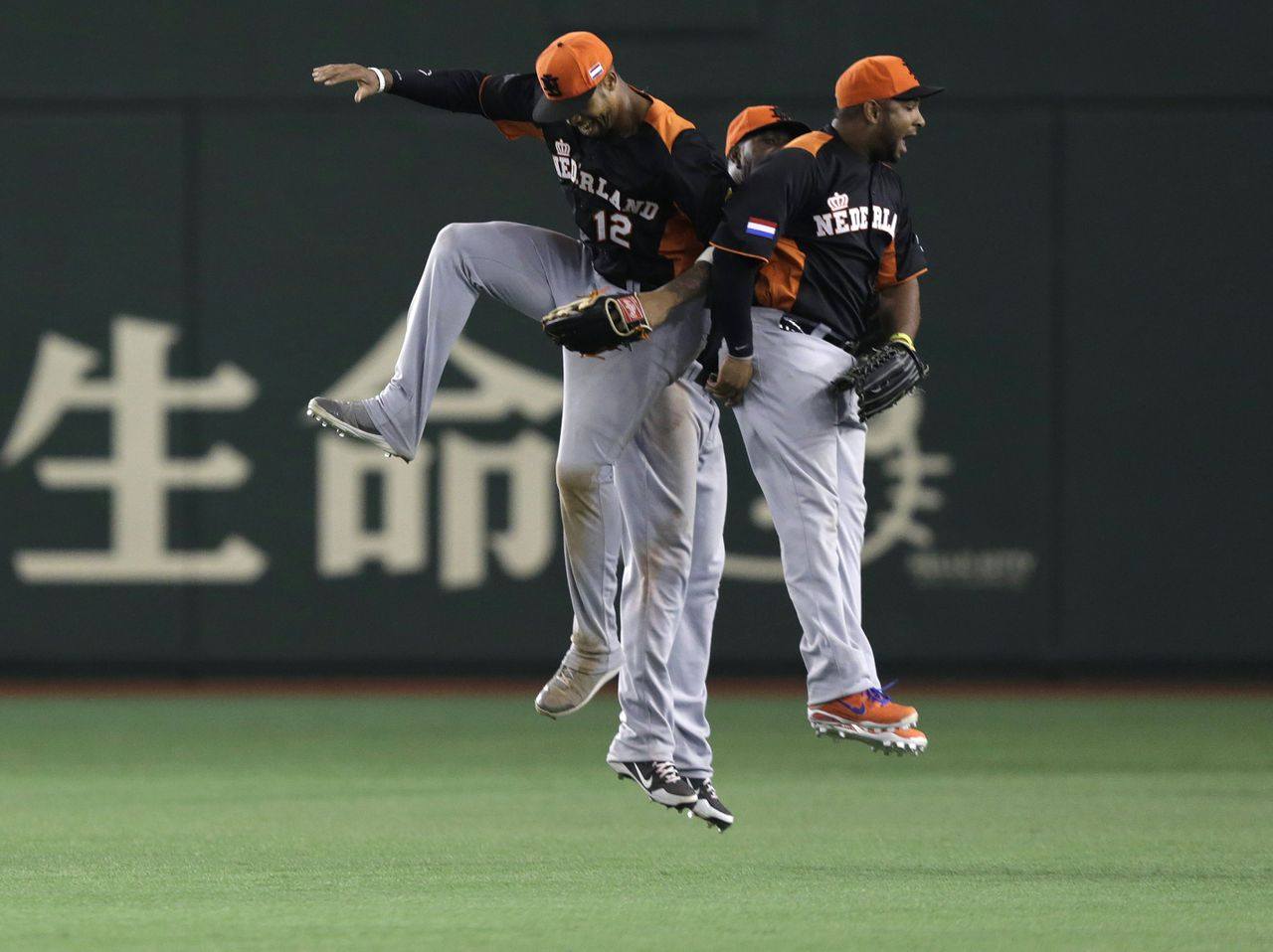 Netherlands' Wladimir Balentien (R), Roger Bernadina (C) and Kalian Sams celebrate after defeating Cuba at the World Baseball Classic (WBC) second round game in Tokyo March 8, 2013. REUTERS/Toru Hanai (JAPAN - Tags: SPORT BASEBALL)