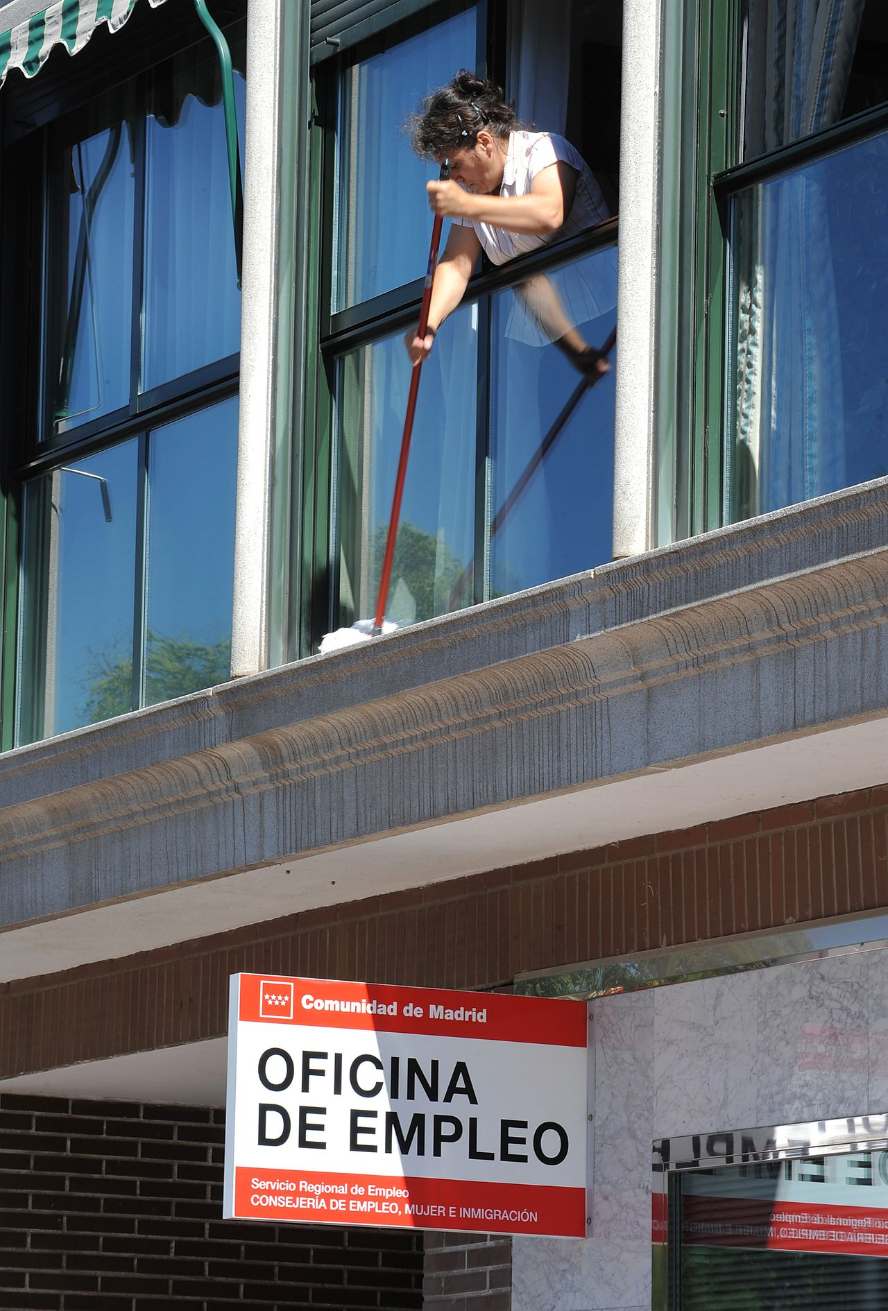 A woman cleans her window ledge above an employment office in Madrid, Spain, on Tuesday, June 15, 2010. Spanish Deputy Finance Minister Carlos Ocana said the country's 20 percent unemployment level is unsustainable. Photographer: Denis Doyle/Bloomberg