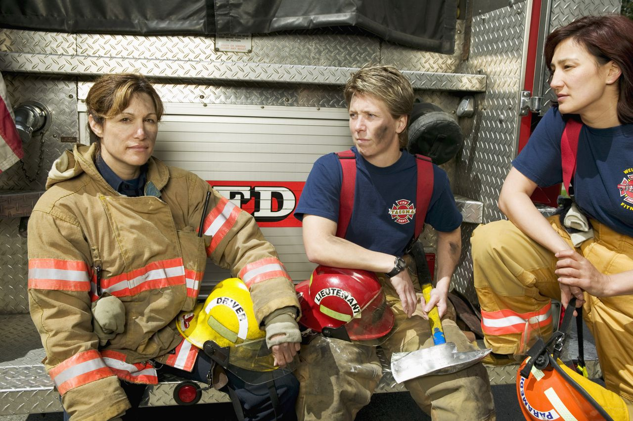 Closeup of three female firefighters --- Image by © Big Cheese Photo/Corbis