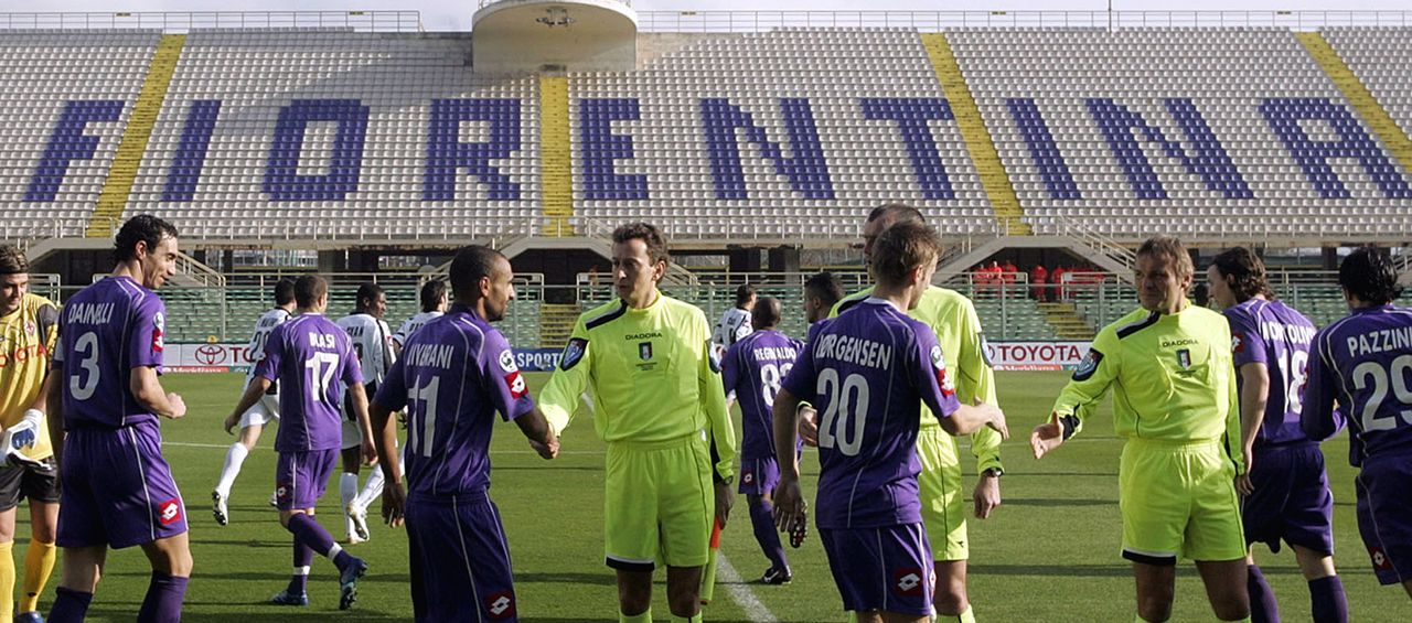 Lege tribunes in Italiaanse stadions Florence, 12 febr. Vier wedstrijden in de Italiaanse Serie A werden gisteren, ruim een week na de rellen op Sicilië, zonder publiek gespeeld. Onder meer het Artemio Franchi-stadion van Fiorentina bleef leeg waardoor de thuiszege op Udinese (2-0) weinig aandacht kreeg. Alleen de stadions die aan de nieuwe veiligheidseisen voldeden, mochten toeschouwers ontvangen. Bij AC Milan, waar de Braziliaan Ronaldo zijn debuut maakte, konden alleen seizoenkaarthouders naar binnen. De thuisploeg won in San Siro met 2-1 van Livorno. Ronaldo, met rugnummer 99, slaagde er niet in om bij zijn debuut voor AC Milan te scoren. Fiorentina soccer club players, in purple, shake hands with field officials, in dayglow green, prior to the start of the Italian Serie A soccer match between Fiorentina and Udinese (players in background in white) in an empty Artemio Franchi stadium, in Florence central Italy, Sunday Feb. 11, 2007. The weekend's league soccer matches were played in stadiums with limited access or fully closed by inspectors for safety reasons. The decision was taken following last week's rioting during the Serie A top division soccer match between Catania and Palermo, which left Italian Police officer Filippo Raciti killed. (AP Photo/Fabrizio Giovannozzi)
